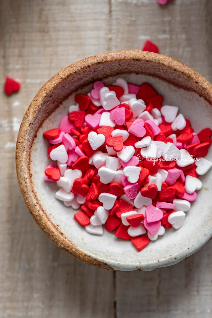 Small bowl of Valentine's Day heart sprinkles Homemade red velvet cupcakes with one opened and half eaten with a small bowl of Valentine's Day sprinkles on light wood background | All images © Beyond the Butter®