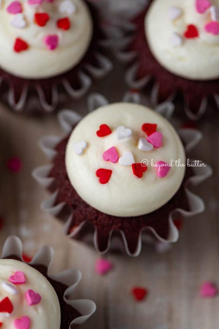 Homemade red velvet cupcakes with cream cheese frosting topped with heart sprinkles on a light wood background | All images © Beyond the Butter®