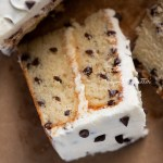 Slice of 2 layer chocolate chip cake on it's side on a brown paper background | © Beyond the Butter®