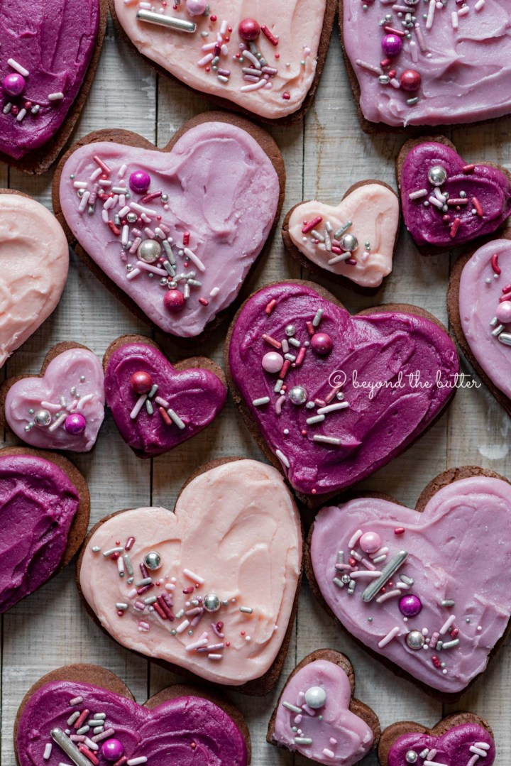 Decorated chocolate cut out sugar cookies on a light wood colored background | All Images © Beyond the Butter®