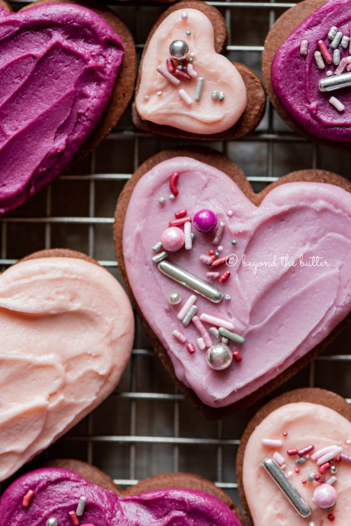 Closeup of decorated chocolate cut out sugar cookies on a wire cooling rack on light wood colored background | All Images © Beyond the Butter®