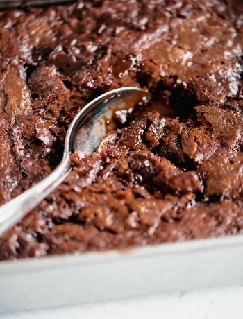 "Close up of Hot Fudge Pudding Cake | Close up shot of a spoon taking a scoop out of the 8"" x"" pan of hot fudge pudding mix 
