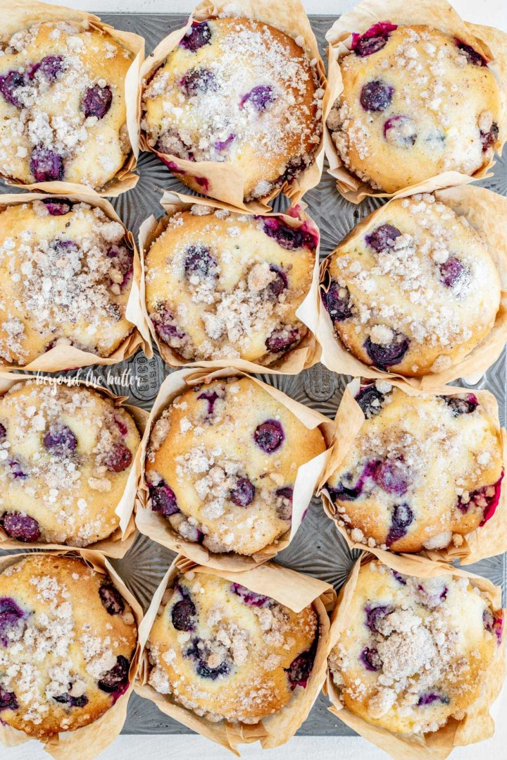 Overhead image of bakery style lemon blueberry streusel muffins in a muffin tin | All Images © Beyond the Butter™