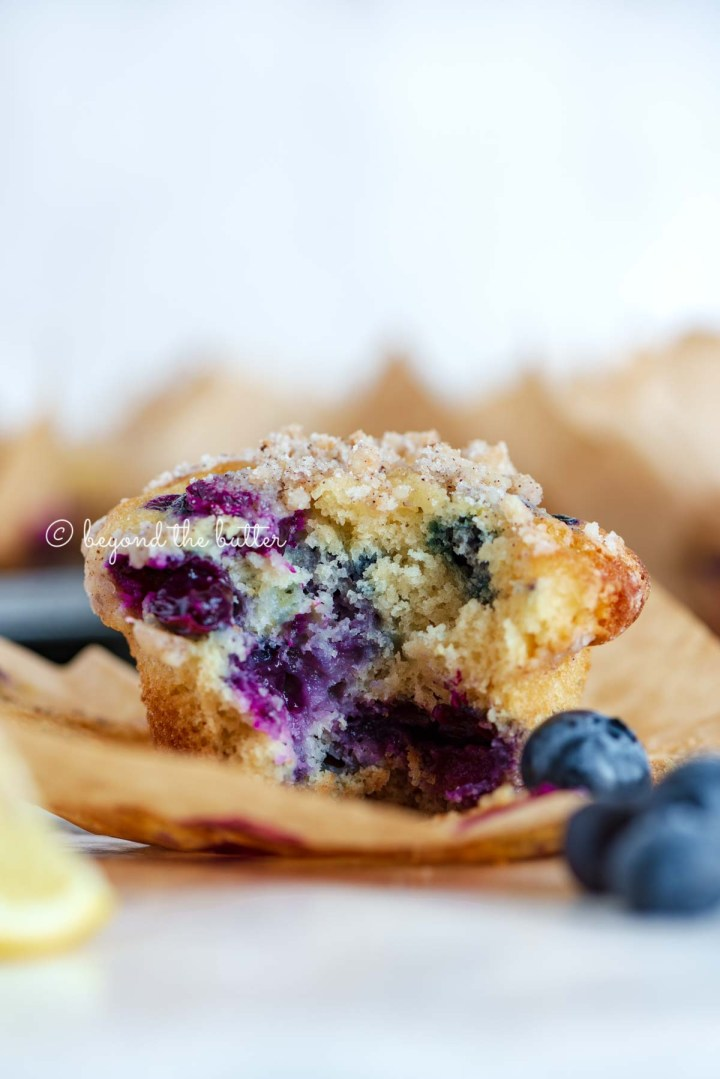 Unwrapped and half eaten lemon blueberry streusel muffin with lemon wedges and blueberries around it | All images © Beyond the Butter®