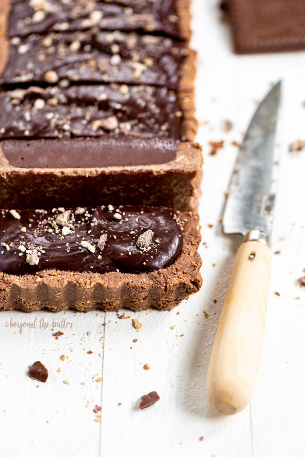 No-bake Dark Chocolate Tart | Angled image of cut slices of no-bake dark chocolate tart with the cutting knife laying beside it | Image and Copyright Policy: © Beyond the Butter, LLC