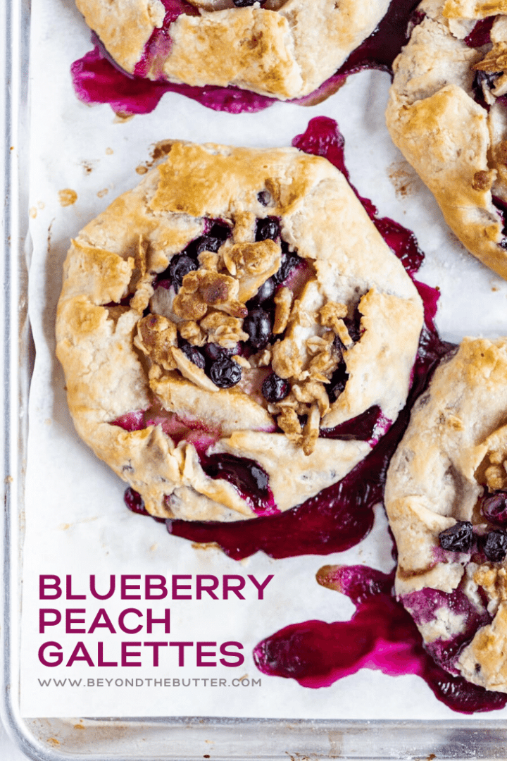 Overhead image of freshly made blueberry peach galettes on a baking sheet | All Images © Beyond the Butter™