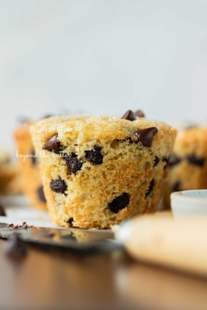Single unwrapped bakery style chocolate chip muffin on a flattened muffin liner with white background   © Beyond the Butter®