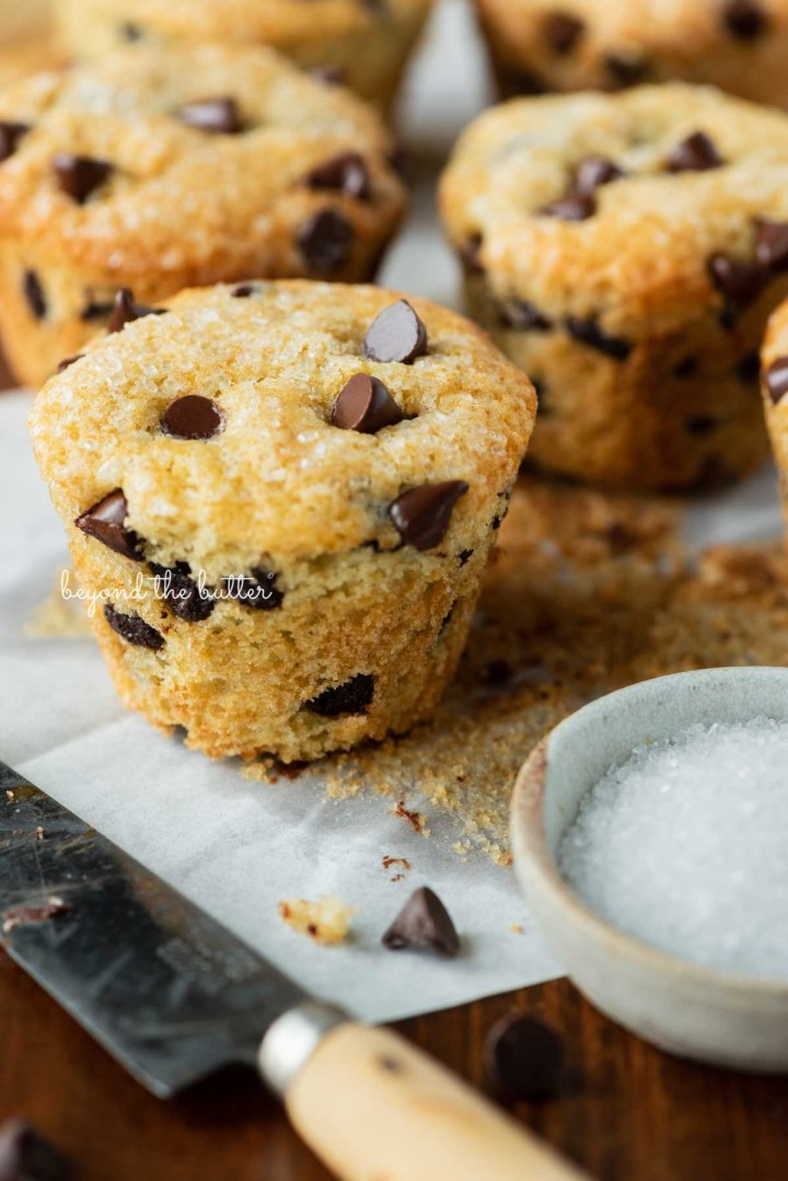 Bakery style chocolate chip mufins unwrapped with a small dipping bowl of sparkling sugar nearby   © Beyond the Butter®