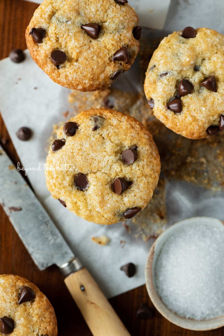 Unwrapped bakery style chocolate chip muffins on flattened muffin liners on a dark background   © Beyond the Butter®