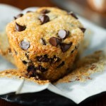 Unwrapped bakery style chocolate chip muffin on flattened muffin linerand black dessert plate   © Beyond the Butter®