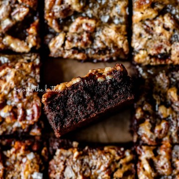 Salted pecan pie brownies placed on brown parchment paper with the center brownie placed on its side   © Beyond the Butter®