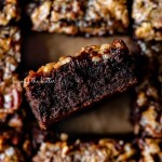 Salted pecan pie brownies placed on brown parchment paper with the center brownie placed on its side | © Beyond the Butter®