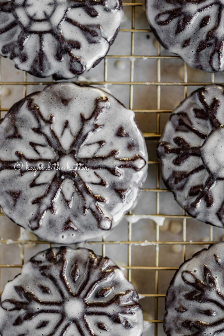Overhead closeup image of homemade oreo snowflake cookies on a wire cooling rack | All Images © Beyond the Butter®