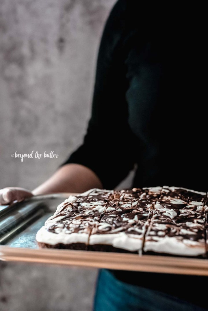 Image of woman holding a try of Chocolate Peppermint Swirled Brownies | All Images © Beyond the Butter, LLC