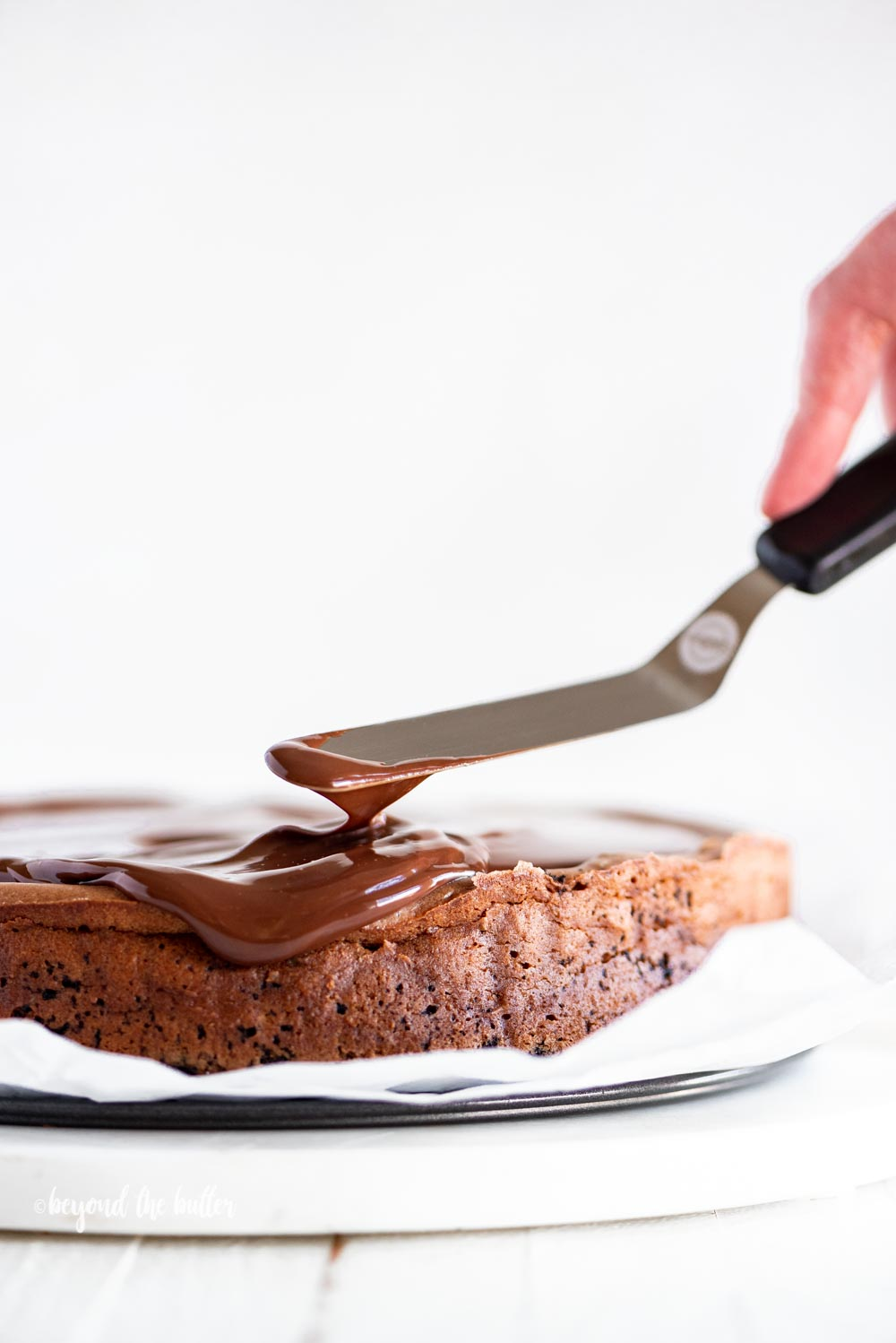 Using an offset spatula to spread out the dark chocolate ganache on top of the Triple Chocolate Mocha Cheesecake | All Images © Beyond the Butter, LLC