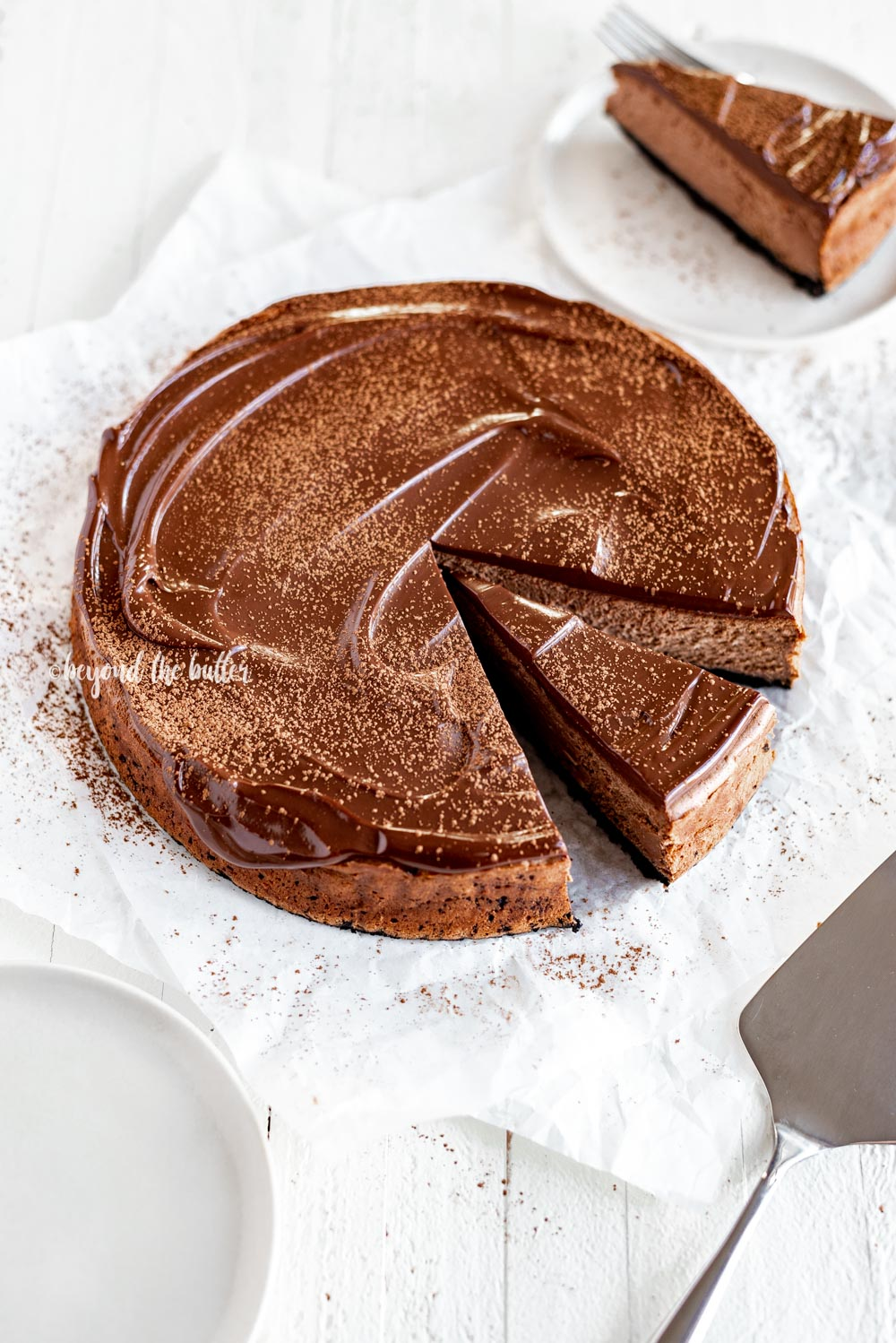 Overhead angled image of Triple Chocolate Mocha Cheesecake dusted with cocoa and a slice removed | All Images © Beyond the Butter, LLC
