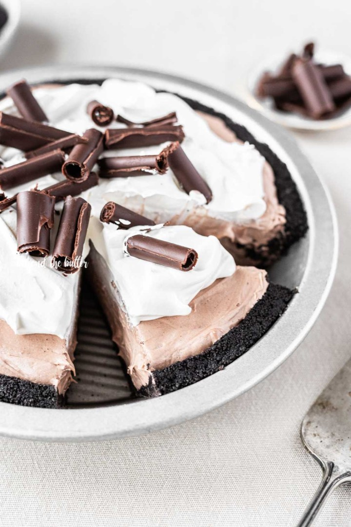 Angled image of sliced no-bake chocolate cream pie with chocolate wafer crust and garnished with Cool Whip and chocolate curls | All Images © Beyond the Butter™