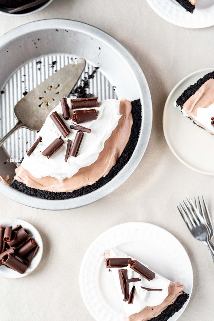 Overhead image of sliced no-bake chocolate cream pie with slices of pie on dessert plates next to it | All Images © Beyond the Butter™