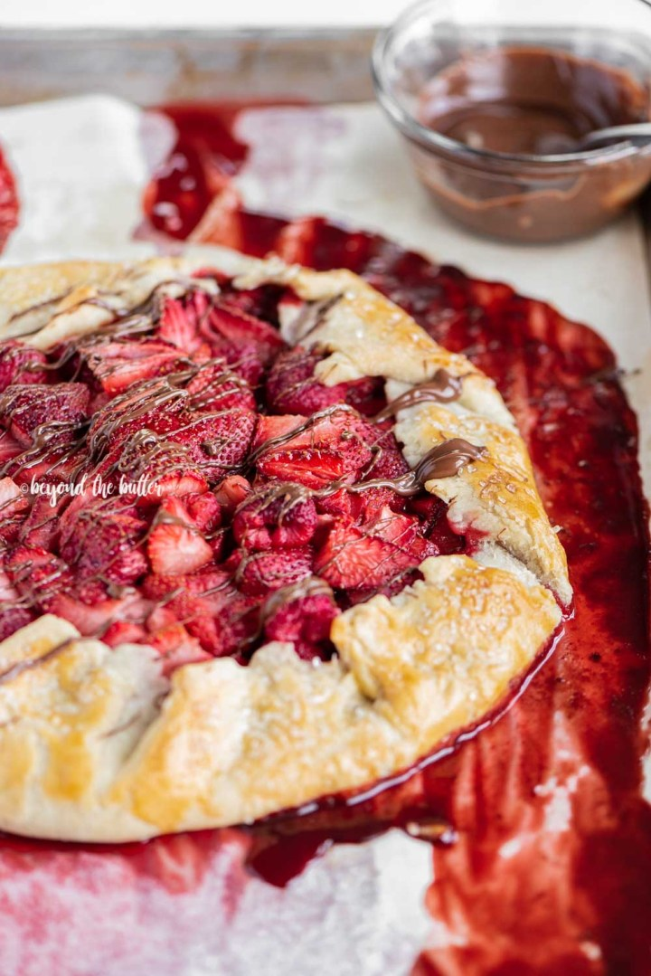 Angled close up image of a Berry Nutella Galette on a baking sheet with Nutella drizzled over the top | All Images © Beyond the Butter™