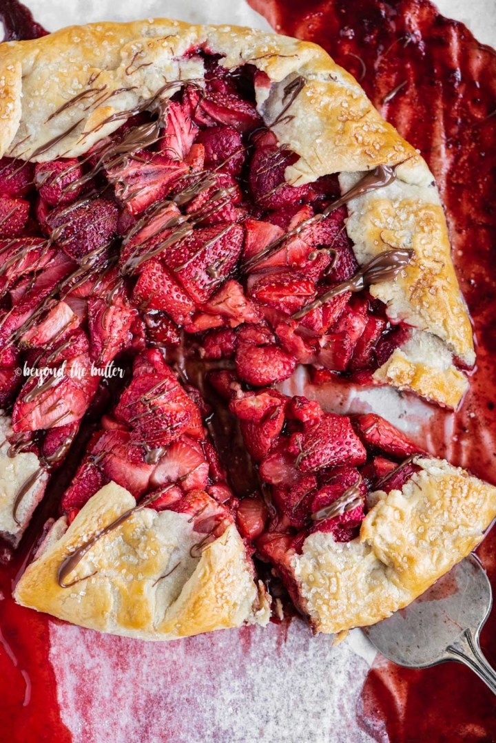 Overhead image of a Berry Nutella Galette on a baking sheet with Nutella drizzled over the top and 2 slices cut | All Images © Beyond the Butter™