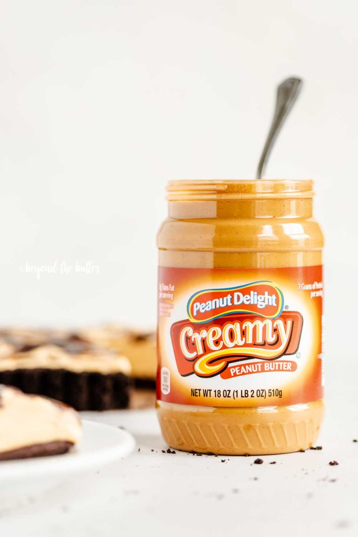 Front view of ALDI's opened jar of Peanut Delight Creamy Peanut Butter next to a chocolate peanut butter swirl tart | All Images © Beyond the Butter™