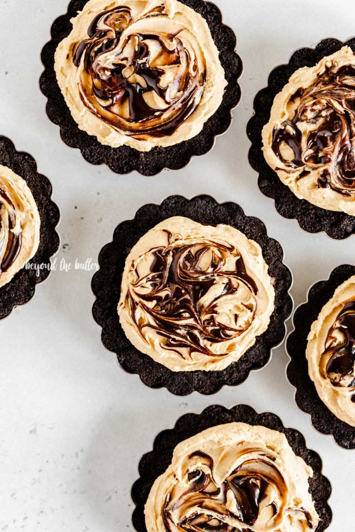 Overhead image of no bake mini chocolate peanut butter swirl tarts | All Images © Beyond the Butter™