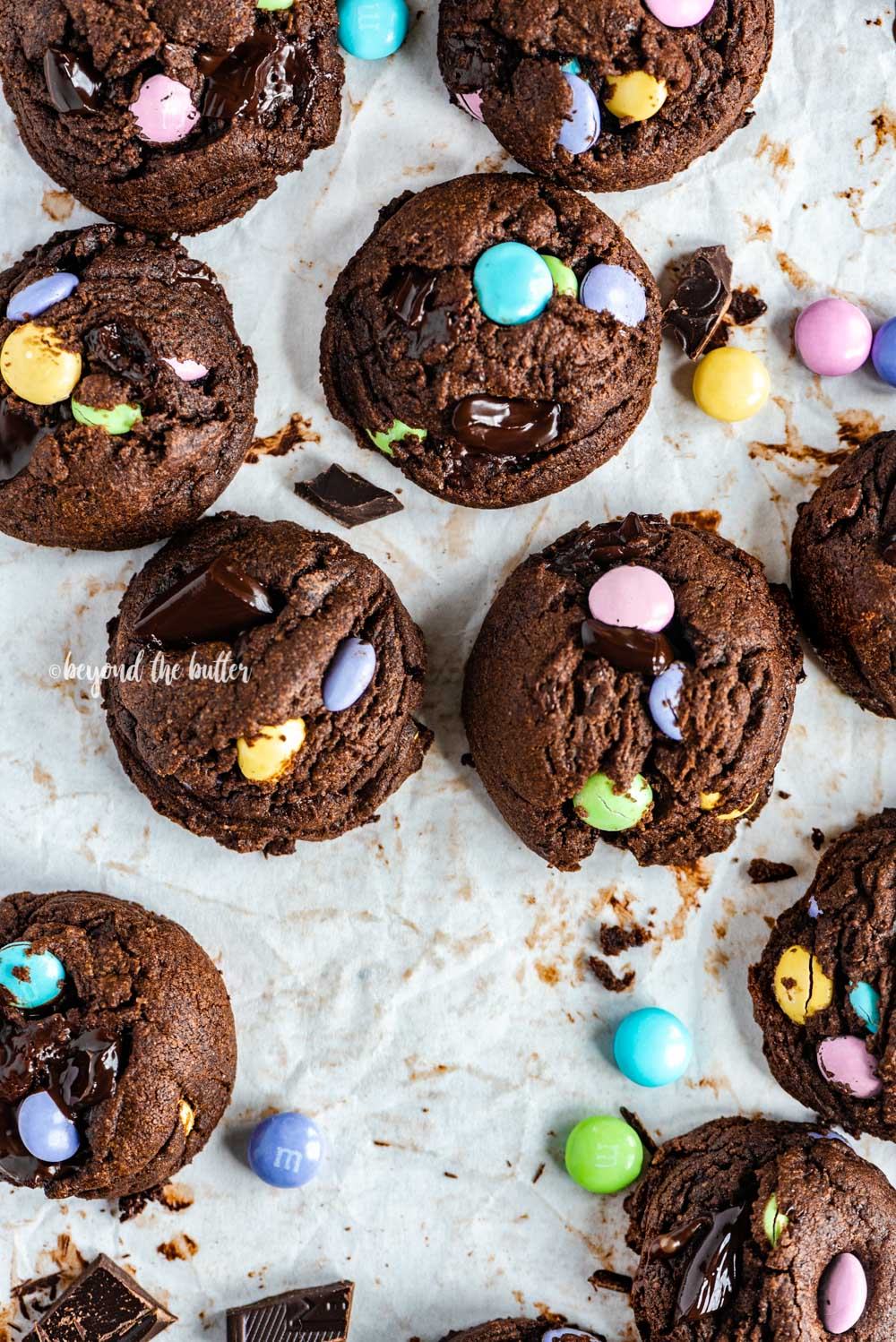 Overhead image of just baked double chocolate chunk m&m cookies on a parchment lined baking sheet | All Images © Beyond the Butter™