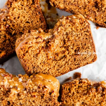 Closeup overhead image of slices of salted caramel banana nut bread on parchment paper | All Images © Beyond the Butter™