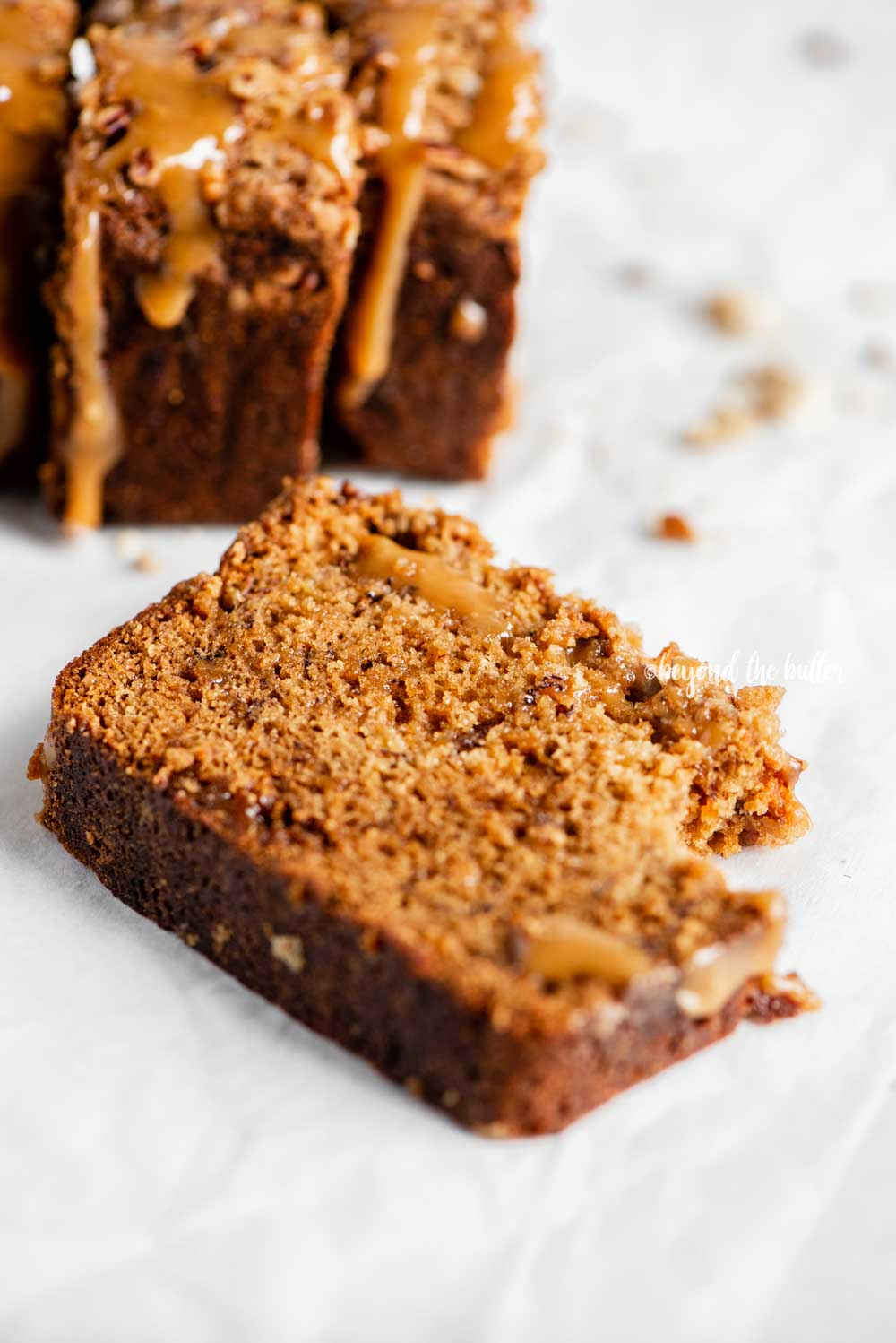 Angled image of slices of salted caramel banana nut bread on parchment paper with a bread knife next to it   All Images © Beyond the Butter™