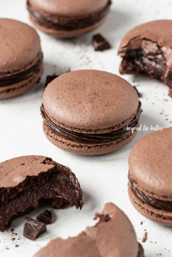 Scattered dark chocolate macarons with some broken or pulled apart | All Images © Beyond the Butter™