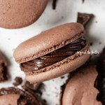 Overhead image of scattered dark chocolate macarons with close up and centered on its side | All Images © Beyond the Butter™