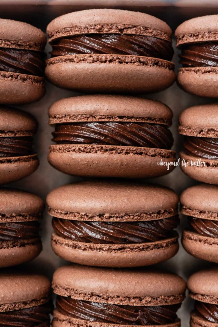 Small baking tray lined with dark chocolate macarons | All Images © Beyond the Butter™