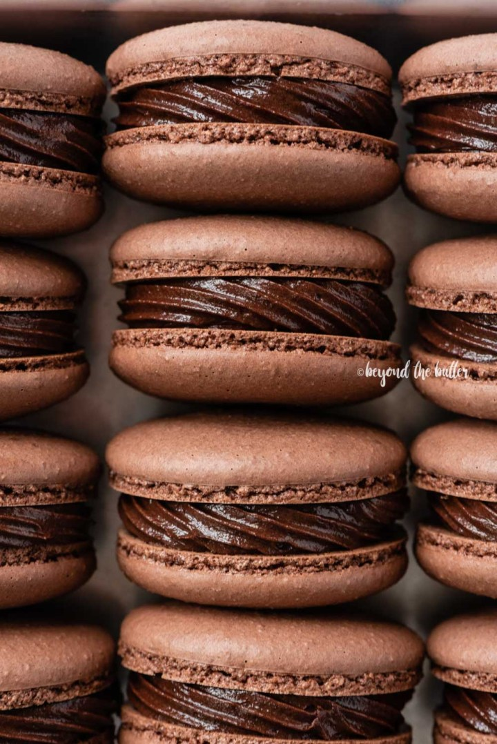 Small baking tray lined with dark chocolate macarons   All Images © Beyond the Butter™