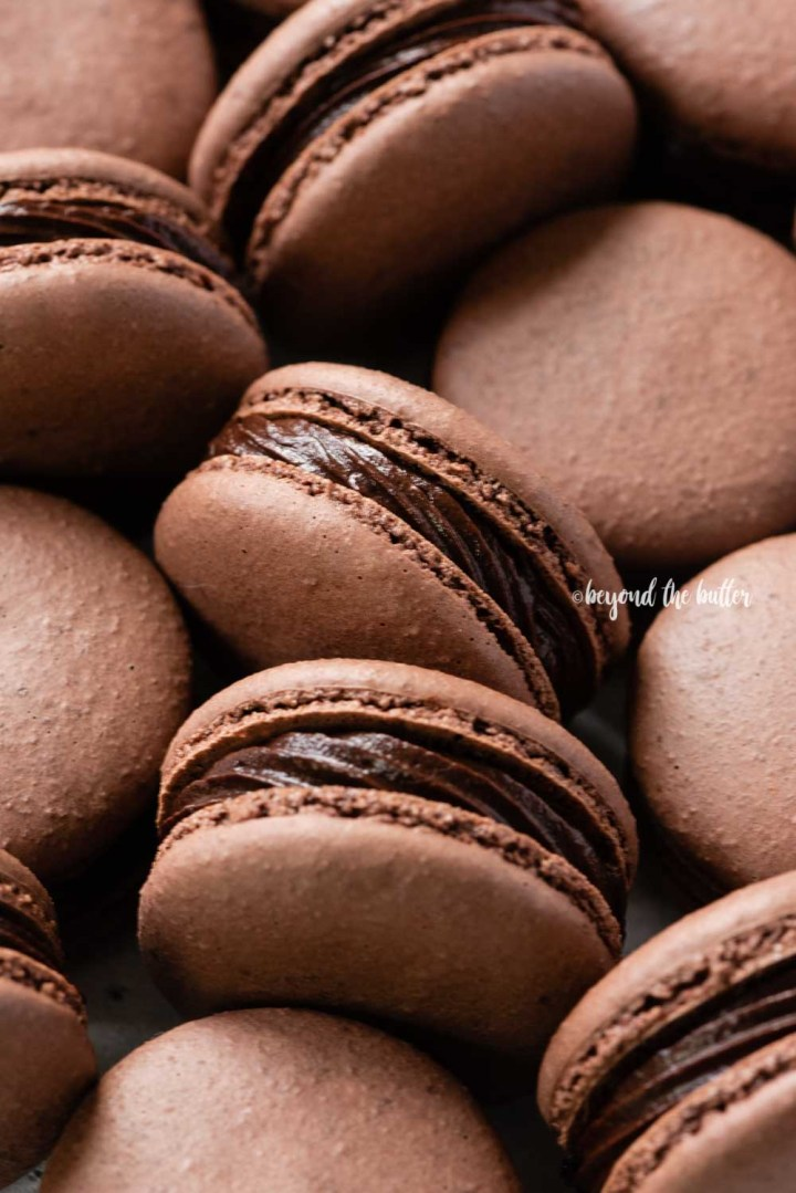 Angled image of randomly placed dark chocolate macarons | All Images © Beyond the Butter™