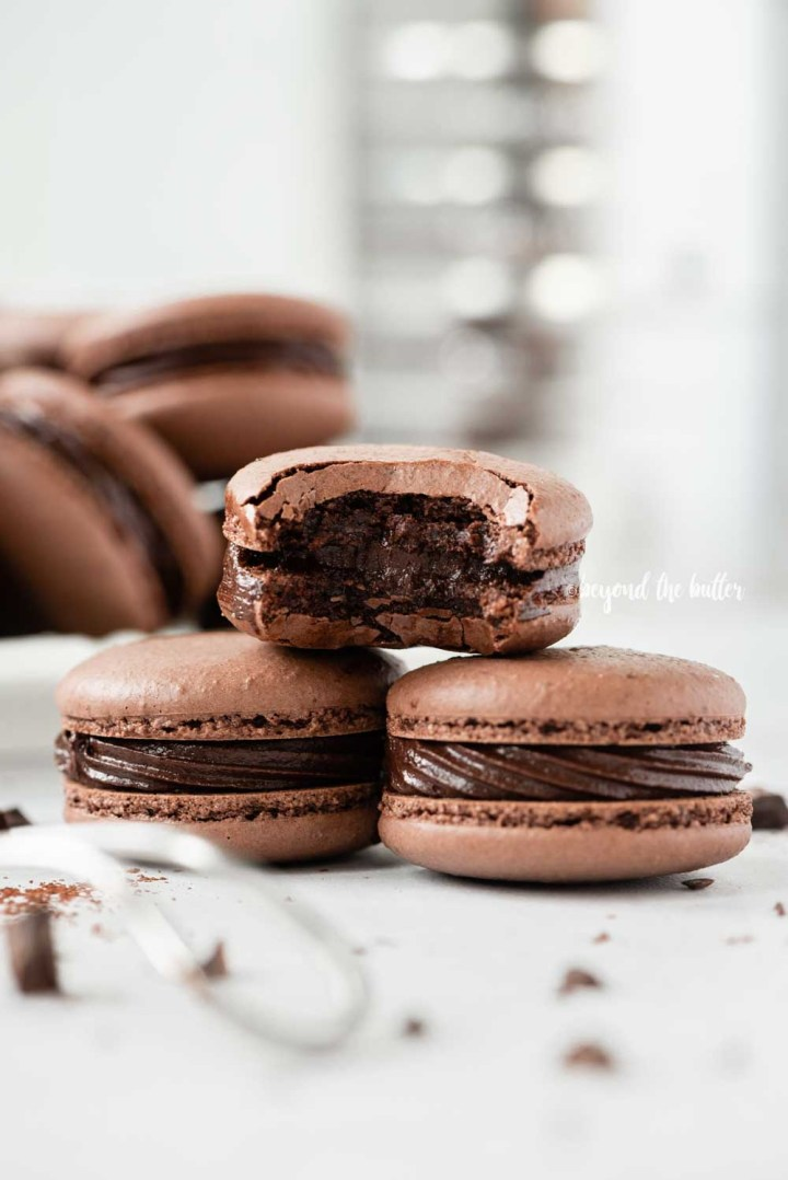 Small stack of chocolate macarons with a bite taken out of the top macaron with a bigger stack in the background with a sifter | All Images © Beyond the Butter™