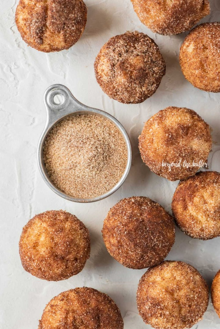 Overhead image of mini french breakfast puffs on a white background with a measuring cup filled with cinnamon sugar mix | All Images © Beyond the Butter™
