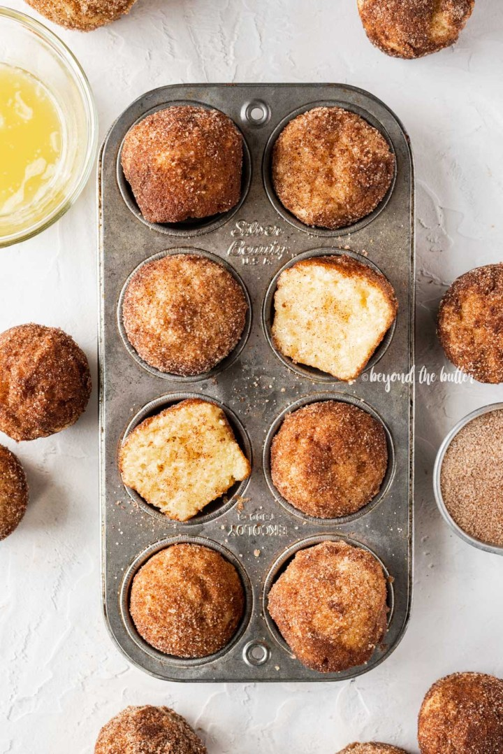 Overhead image of mini french breakfast puffs laid on top of a mini muffin tin with bowls of melted butter and cinnamon sugar around it | All Images © Beyond the Butter™