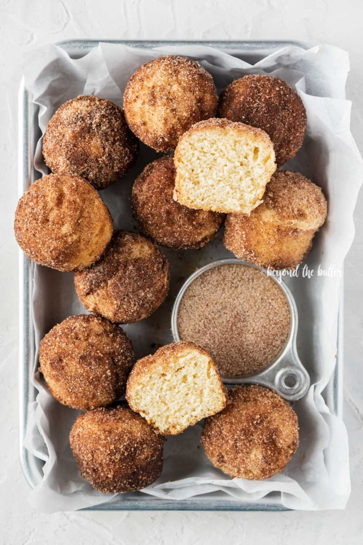 Overhead image of mini french breakfast puffs piled onto a parchment lined baking sheet with a bowl of cinnamon sugar | All Images © Beyond the Butter™