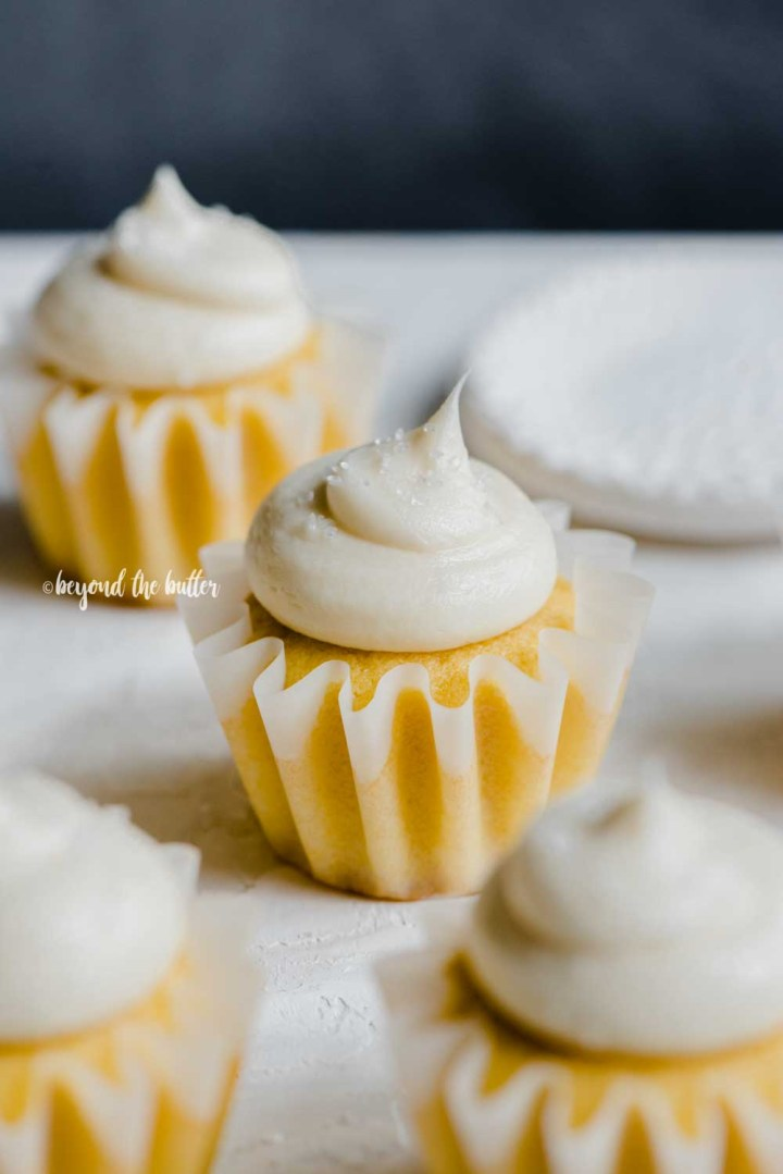 Angled image of vanilla cupcakes with dark background | All Images © Beyond the Butter™