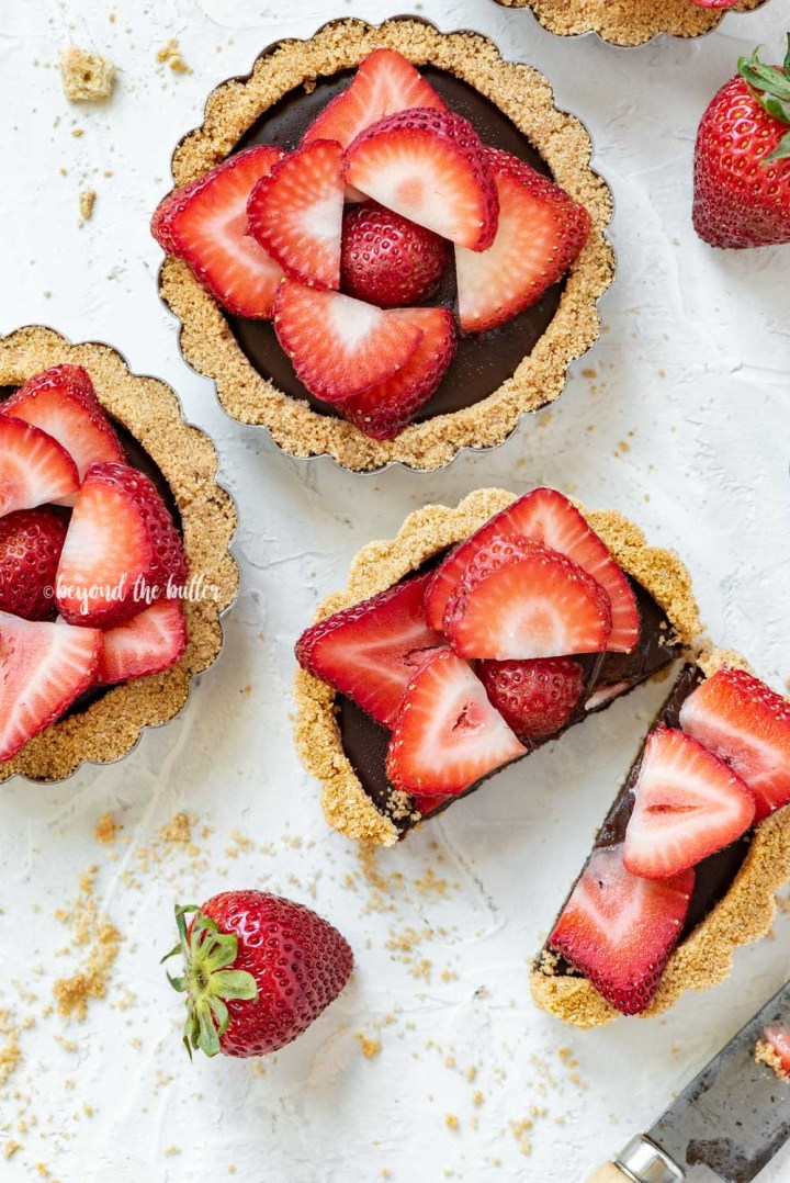 Overhead image of mini strawberry nutella tarts on white stucco background with one sliced in half and opened | All Images © Beyond the Butter™