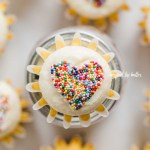 Overhead image of sprinkled heart cupcakes on white/grya background | All Images © Beyond the Butter™