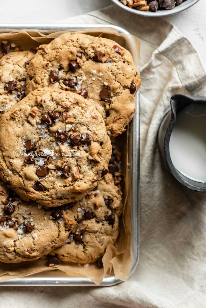 Large almond butter chocolate chip pecan cookies stacked on a baking sheet with a small pitcher of milk and bowl of chocolate chips and pecans nearby| All Images © Beyond the Butter™