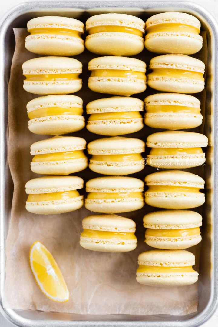 Close up of lemon bar macarons on side on a baking tray | All Images © Beyond the Butter™