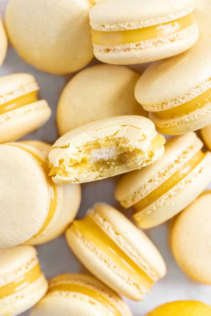 Randomly placed lemon macarons with a bite taken out of the center macaron | All Images © Beyond the Butter™