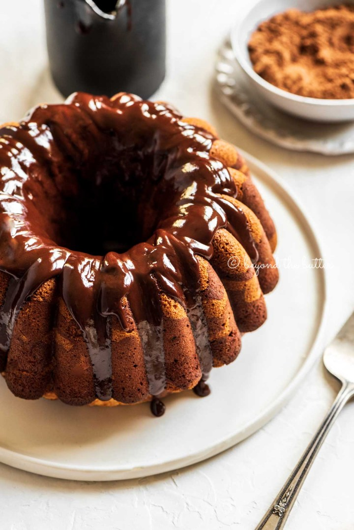 Angled image of chocolate glazed marble bundt cake on black and white cake platter, small bowl of cocoa, and 2 forks | All Images © Beyond the Butter™