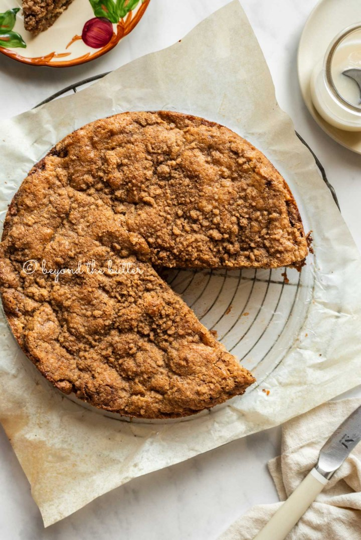 Apple coffee cake on a parchment paper lined wire cooling rack with a slice removed and a simple vanilla glaze, dessert plates, and a knife to the side | All Images © Beyond the Butter™