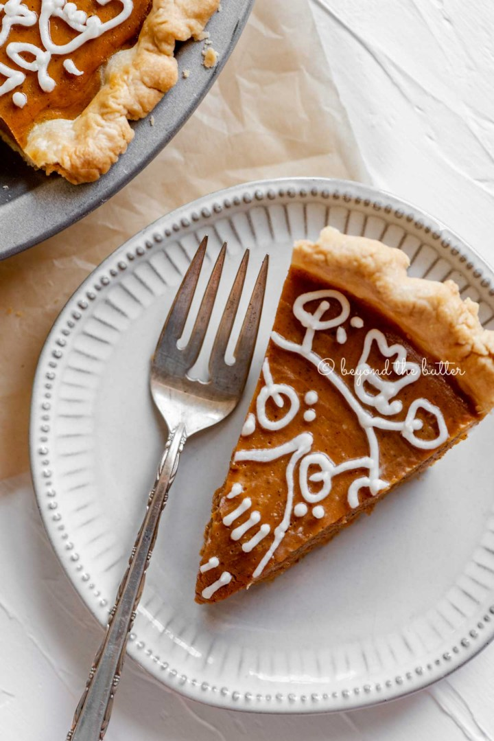 Slice of pumpkin pie on a dessert plate with a fork resting on the plate and pie plate off to the side | All Images © Beyond the Butter™