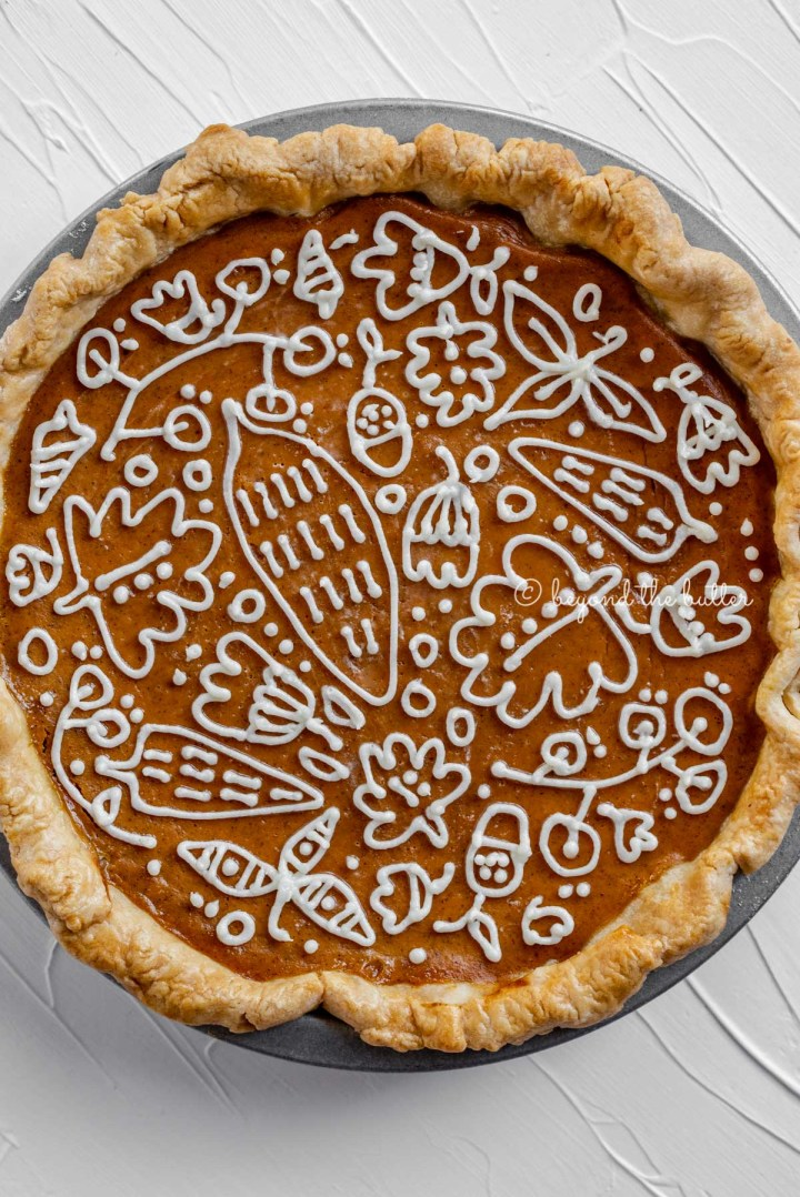 Overhead image of pumpkin pie with a piped cream cheese frosting decoration | All images © Beyond the Butter™
