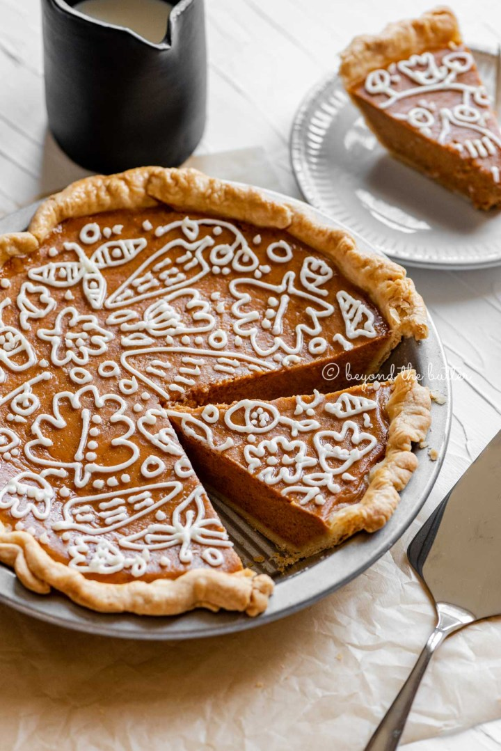 Angled image of cut pumpkin pie with a piped cream cheese frosting decoration surrounded by pie server, cinnamon sticks, plates, and small pitcher of milk | All images © Beyond the Butter™