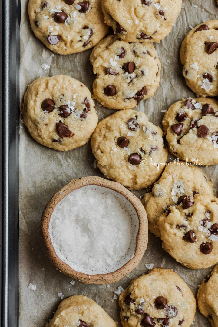 Freshly baked salted chocolate chip shortbread cookies cooling on parchment paper lined cookie sheet | All Images © Beyond the Butter®